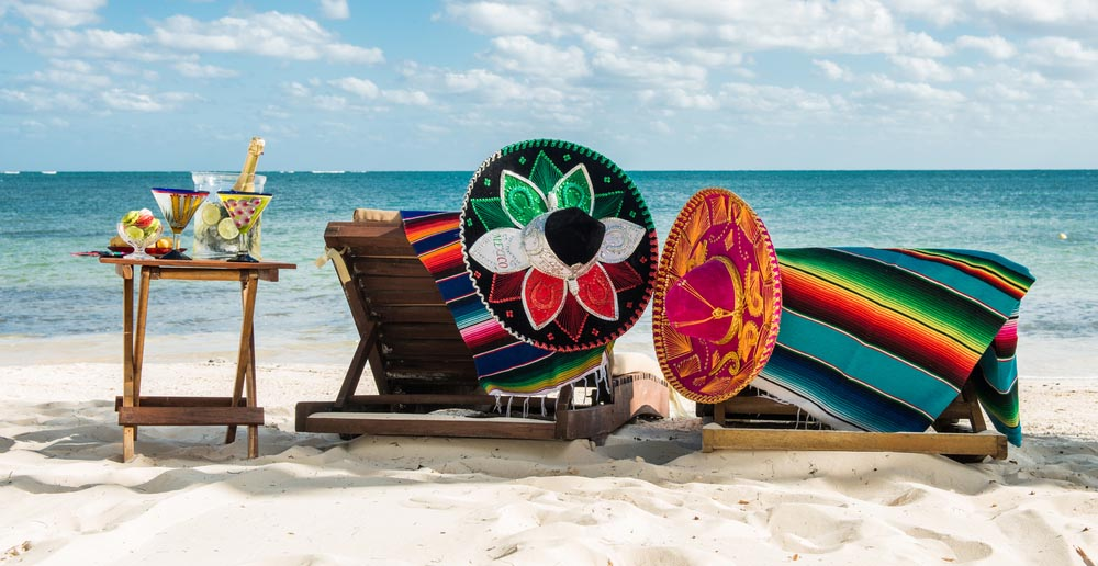 Sombreros, tropical drinks and beach chairs on a beautiful sandy beach